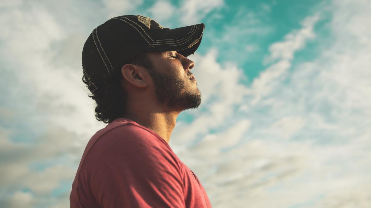 person wearing a baseball cap, eyes closed, facing towards the sun