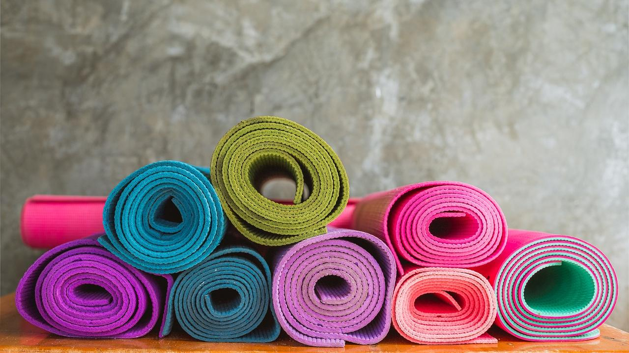 Pile of rolled up yoga mats in various bright colors.