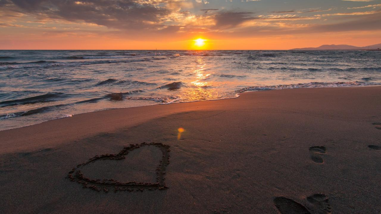 image of a beach at sunset with a heart drawn into the sand