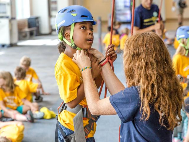 Instructor fastening rock climbing helmet to head of young student.