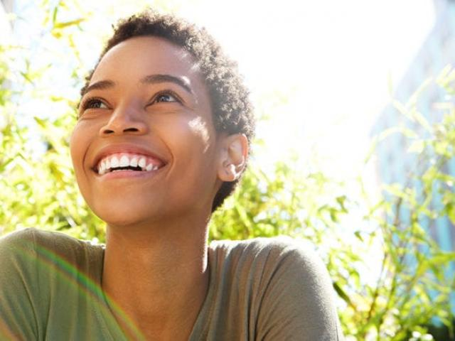 positive looking woman smiling into the sunlight