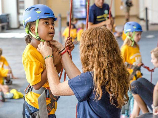 person strapping climbing helmet onto child about to rock climb indoors.
