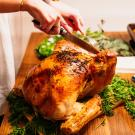 woman carving a cooked turkey at a dinner table