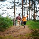 a man and woman walking joyfully in the forest