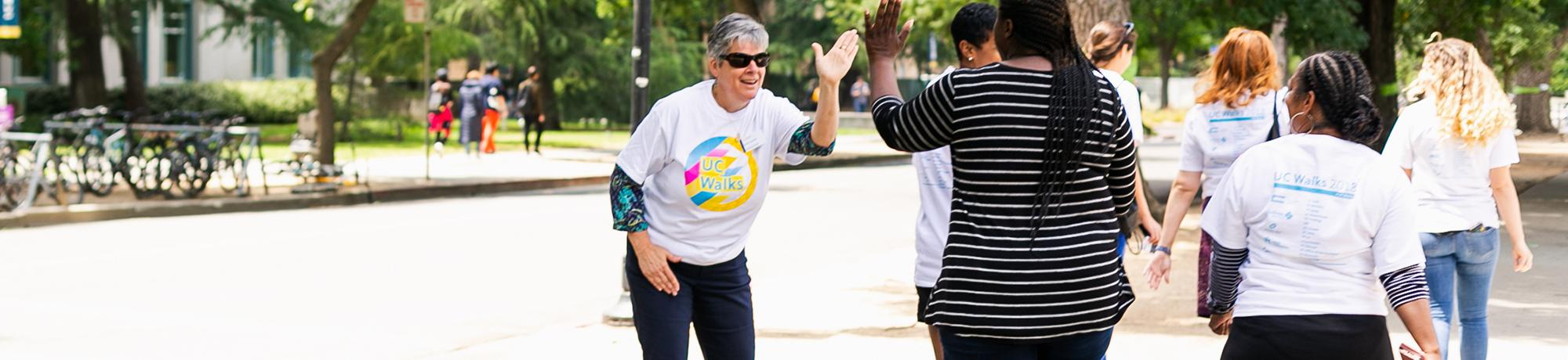 uc davis vc kelly ratliffe giving high fives during a uc walks event